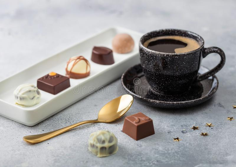 Luxury Chocolate candies in white porcelain plate with cup of black coffee and golden spoon on light table background stock image