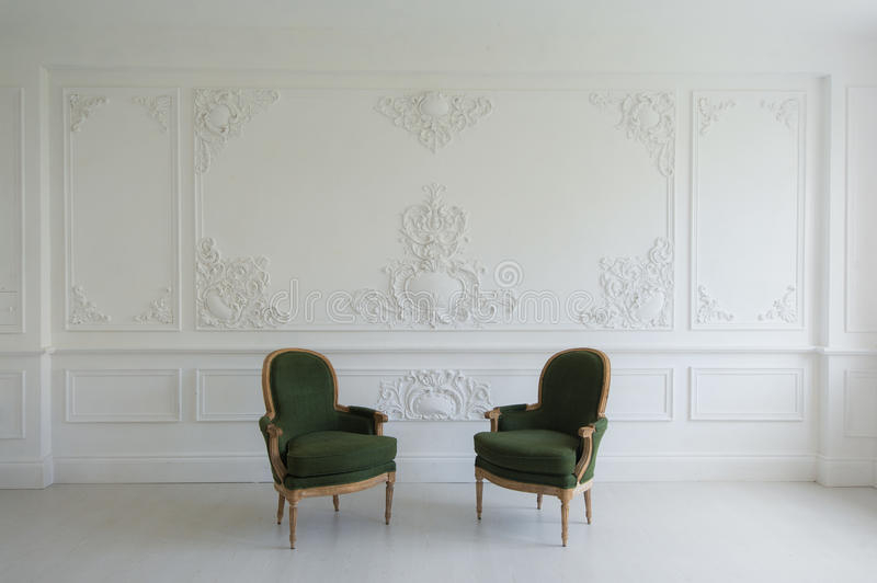 Luxury clean bright white interior with a old antique vintage green chairs over wall design bas-relief stucco mouldings. Roccoco elements stock photography