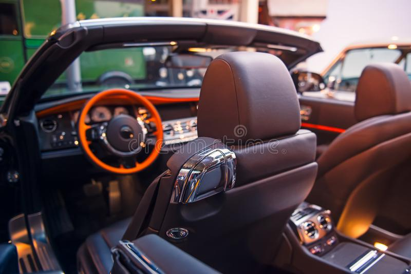 Luxury convertible car interior. Steering wheel, shift lever and dashboard. Driver side view. Selective focus, copy space.  royalty free stock photography