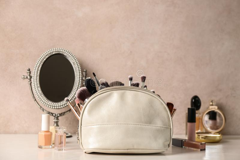 Luxury cosmetics and bag with makeup brushes on dressing table. Space for text royalty free stock images