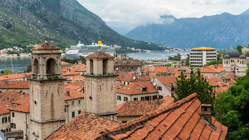A Luxury Cruise Ship in Kotor Montenegro. Liner Seven Seas Voyager in the port. Coast Town in the balkans and orange roof tiles. Travel, harbor, europe, nature stock photo