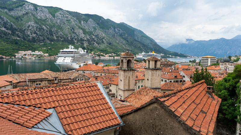 A Luxury Cruise Ship in Kotor Montenegro. Liner Seven Seas Voyager in the port. Coast Town in the balkans and orange roof tiles. Travel, harbor, europe, nature royalty free stock photography