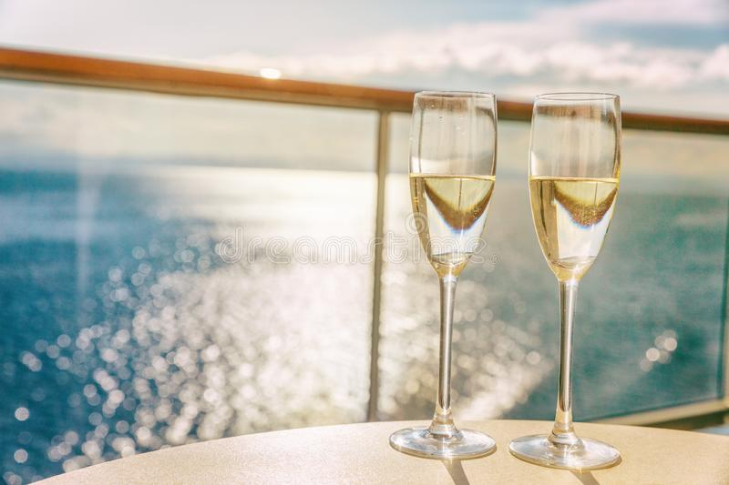 Luxury cruise ship travel champagne glasses on balcony deck with ocean sunset view on Caribbean vacation. Drinks in sun flare on. Cruise holiday destination royalty free stock photography