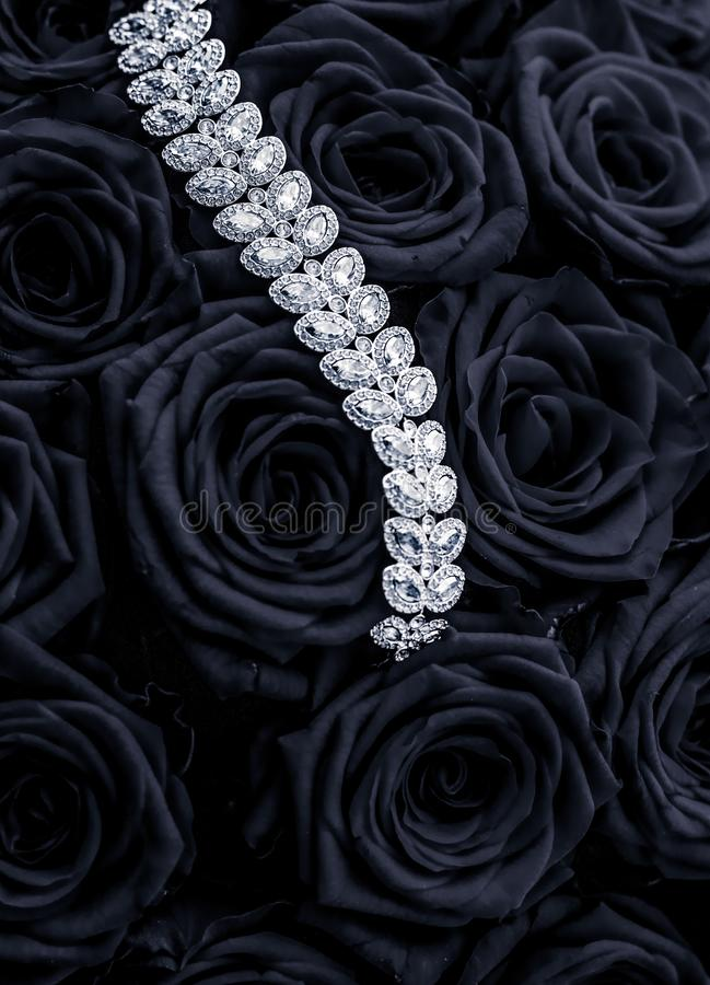 Luxury diamond jewelry bracelet and black roses flowers, love gift on Valentines Day and jewellery brand holiday background design. Luxe branding, glamour royalty free stock photo