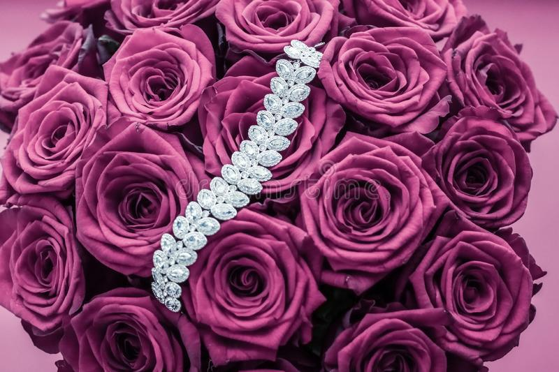 Luxury diamond jewelry bracelet and pink roses flowers, love gift on Valentines Day and jewellery brand holiday background design. Luxe branding, glamour fashion stock images