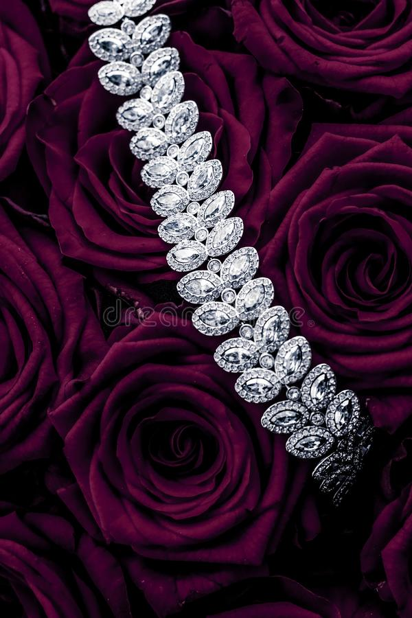 Luxury diamond jewelry bracelet and purple roses flowers, love gift on Valentines Day and jewellery brand holiday background. Luxe branding, glamour fashion and royalty free stock image
