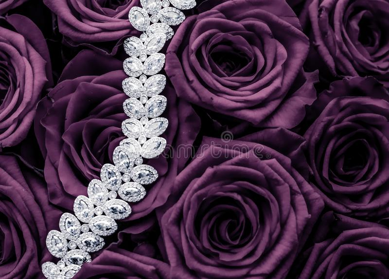 Luxury diamond jewelry bracelet and purple roses flowers, love gift on Valentines Day and jewellery brand holiday background. Luxe branding, glamour fashion and stock images
