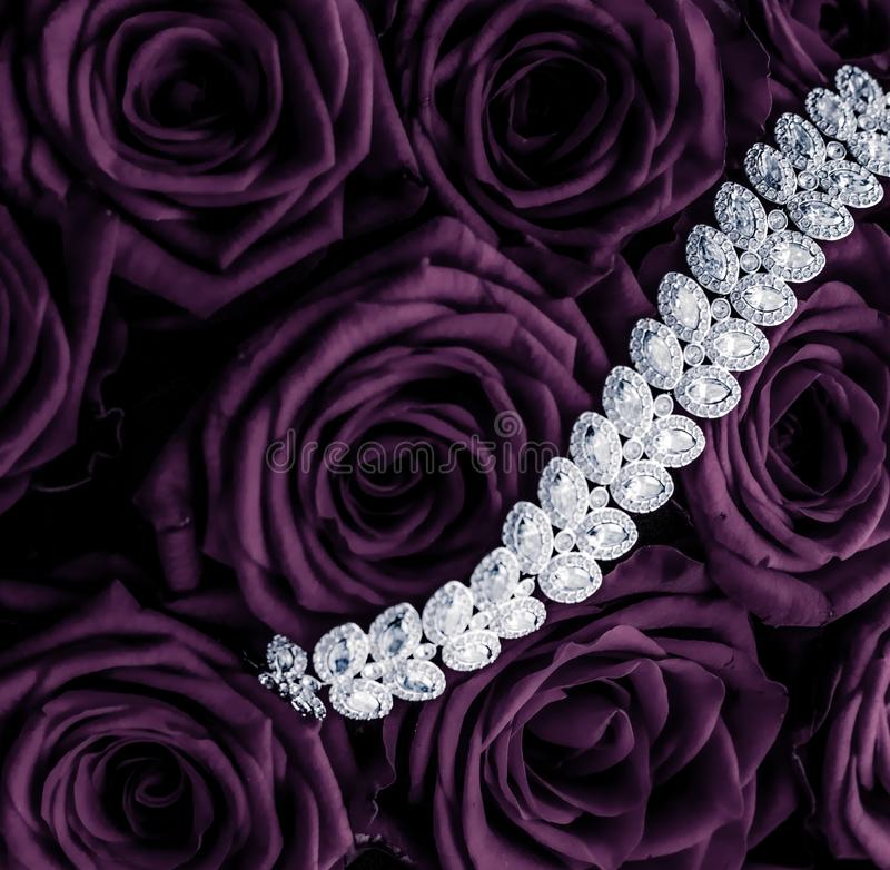 Luxury diamond jewelry bracelet and purple roses flowers, love gift on Valentines Day and jewellery brand holiday background. Luxe branding, glamour fashion and stock image