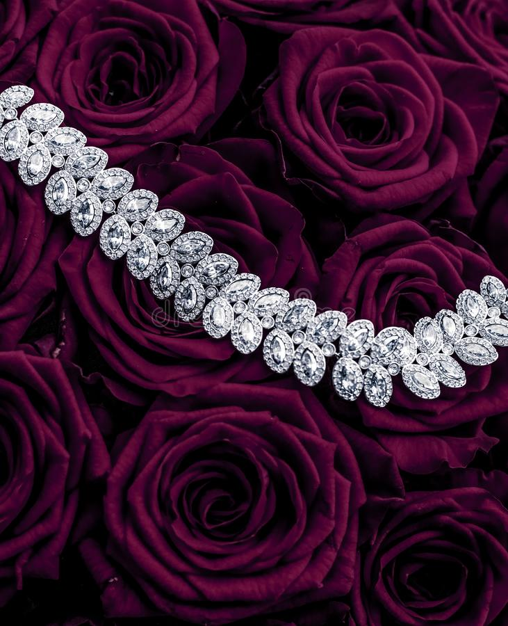 Luxury diamond jewelry bracelet and purple roses flowers, love gift on Valentines Day and jewellery brand holiday background. Luxe branding, glamour fashion and royalty free stock photos