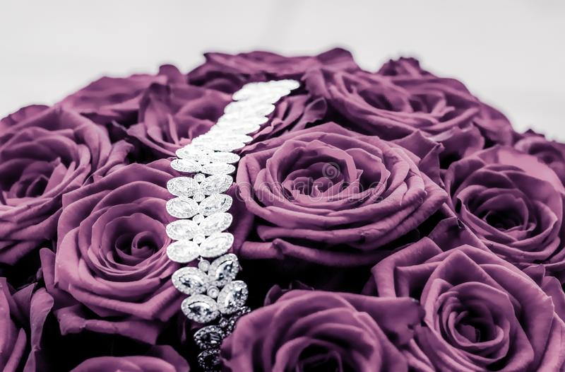 Luxury diamond jewelry bracelet and purple roses flowers, love gift on Valentines Day and jewellery brand holiday background. Luxe branding, glamour fashion and stock photography