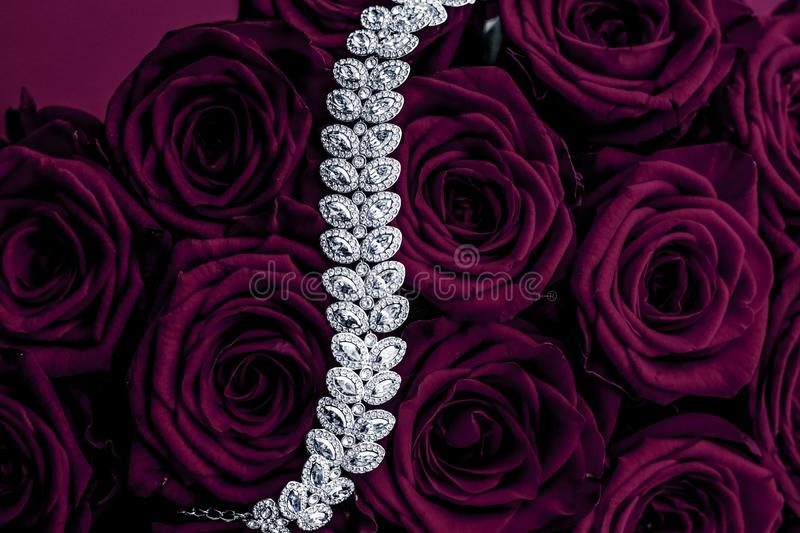Luxury diamond jewelry bracelet and purple roses flowers, love gift on Valentines Day and jewellery brand holiday background. Luxe branding, glamour fashion and royalty free stock photo