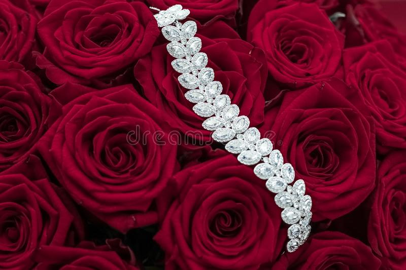 Luxury diamond jewelry bracelet and red roses flowers, love gift on Valentines Day and jewellery brand holiday background design. Luxe branding, glamour fashion royalty free stock photography
