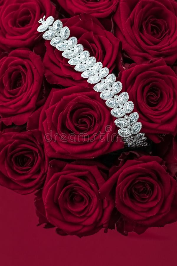 Luxury diamond jewelry bracelet and red roses flowers, love gift on Valentines Day and jewellery brand holiday background design. Luxe branding, glamour fashion stock photography