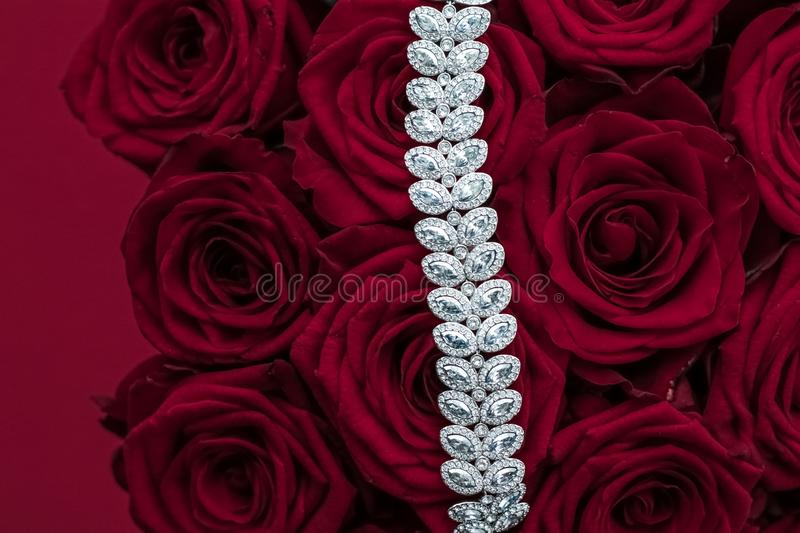 Luxury diamond jewelry bracelet and red roses flowers, love gift on Valentines Day and jewellery brand holiday background design. Luxe branding, glamour fashion stock image