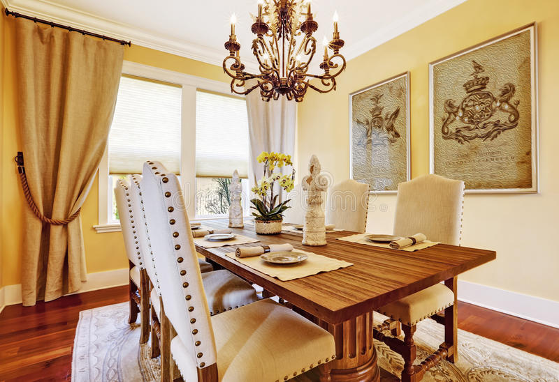 Luxury dining room with carved wood table. Bright luxury dining room with rich carved wood table royalty free stock images