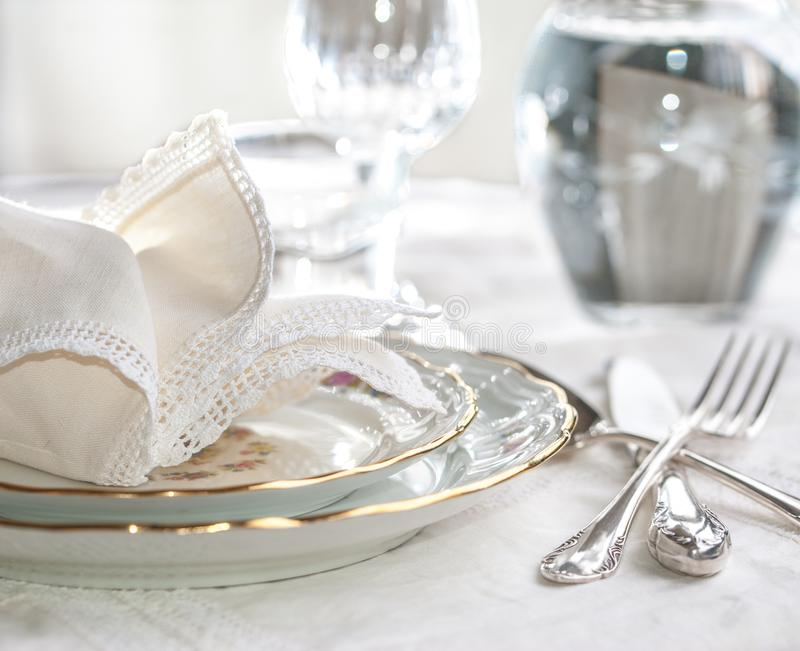 Luxury dinner set with silverware, elegant porcelain dishes, cry. Stal glassware and cream vintage lace napkins royalty free stock image