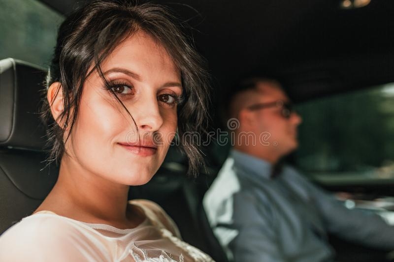 Luxury elegant wedding couple holding hands in stylish black car . gorgeous bride and handsome groom in retro style royalty free stock photography