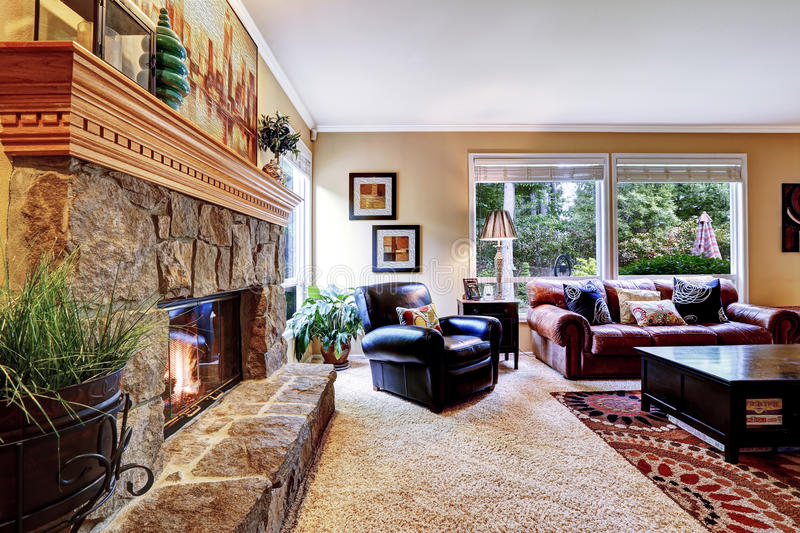 Luxury family room with cozy stone trimmed fireplace. Rich leather couch and armchair create comfort atmosphere stock photo