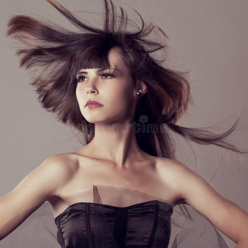 Luxury fashion model with flying hair. Beautiful fashionable girl. Stylish trendy woman stock photography