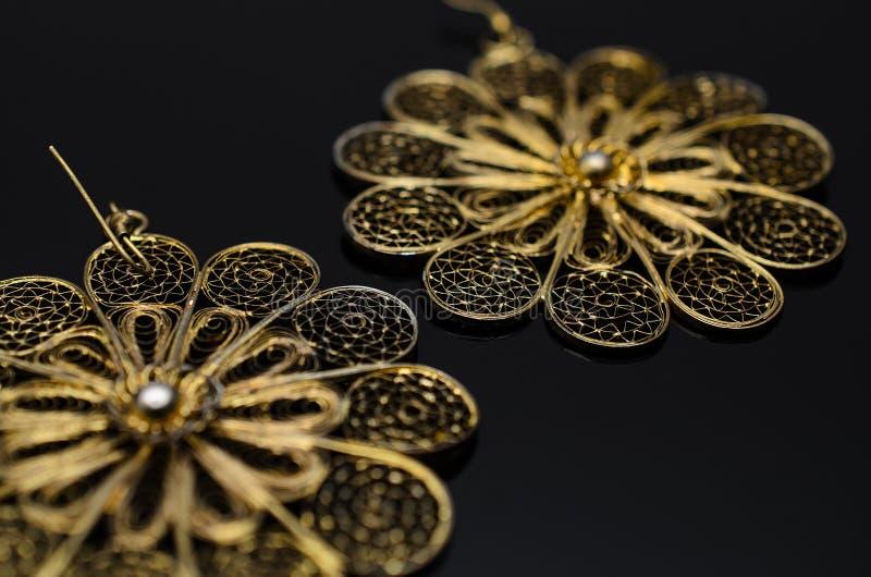 Luxury fashion pearl earrings on black background. Gold fashion earrings on a black background royalty free stock photo