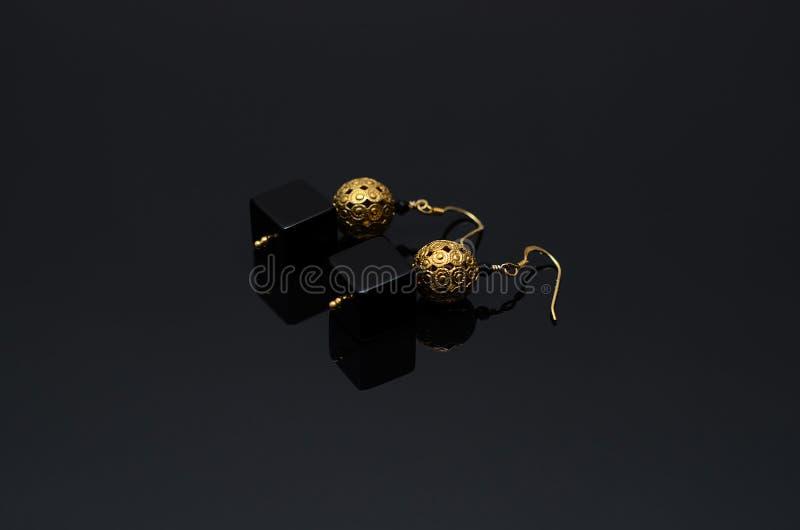 Luxury fashion pearl earrings on black background. Gold fashion earrings on a black background stock photo