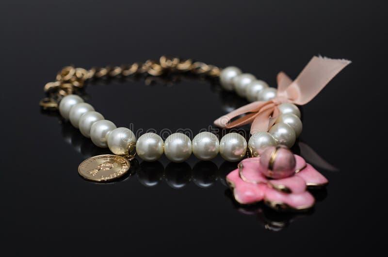 Luxury fashion pearl earrings on black background. Gold fashion bracelet on a black background royalty free stock photo