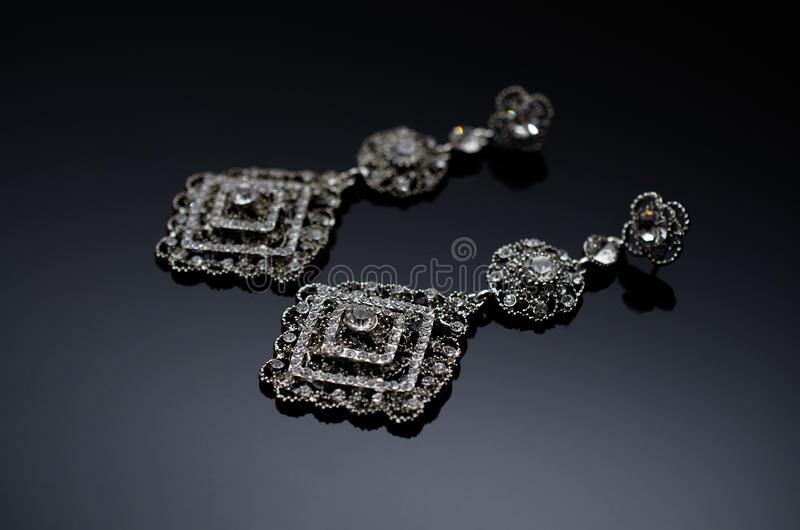 Luxury fashion pearl earrings on black background. Silver fashion earrings on a black background stock photography