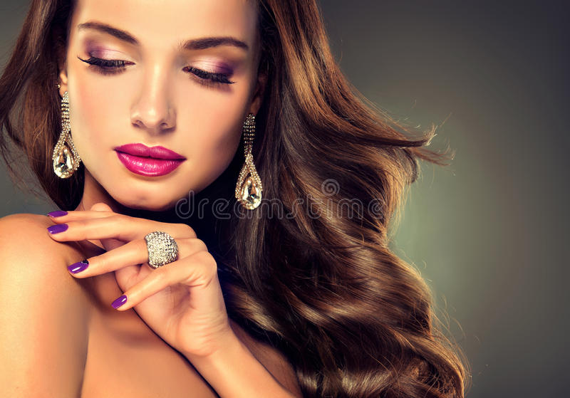 Luxury fashion style.Brunette with long curled hair royalty free stock images