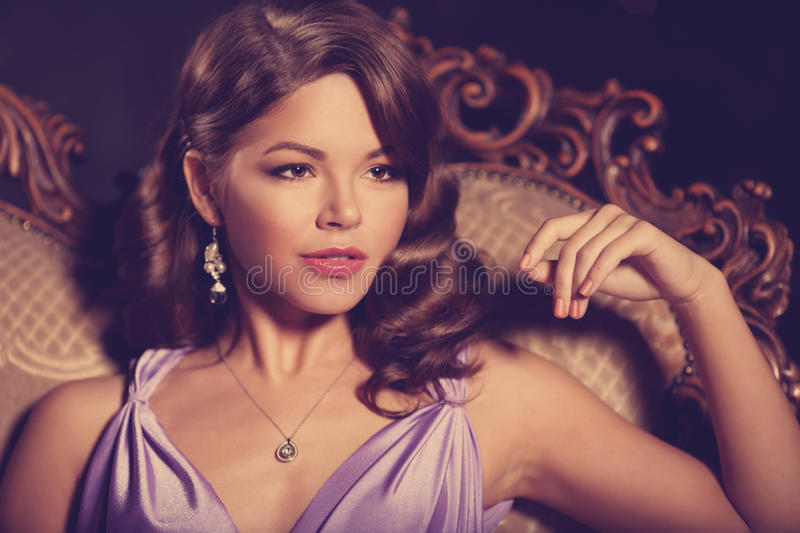 Luxury fashion stylish woman in the rich interior. Beautiful girl with a fashionable hairstyle and makeup chic royalty free stock photography