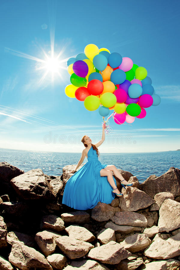 Luxury fashion woman with balloons in hand on the beach against. Luxury fashion stylish woman with balloons in hand on the beach against the sky and the sun in stock image