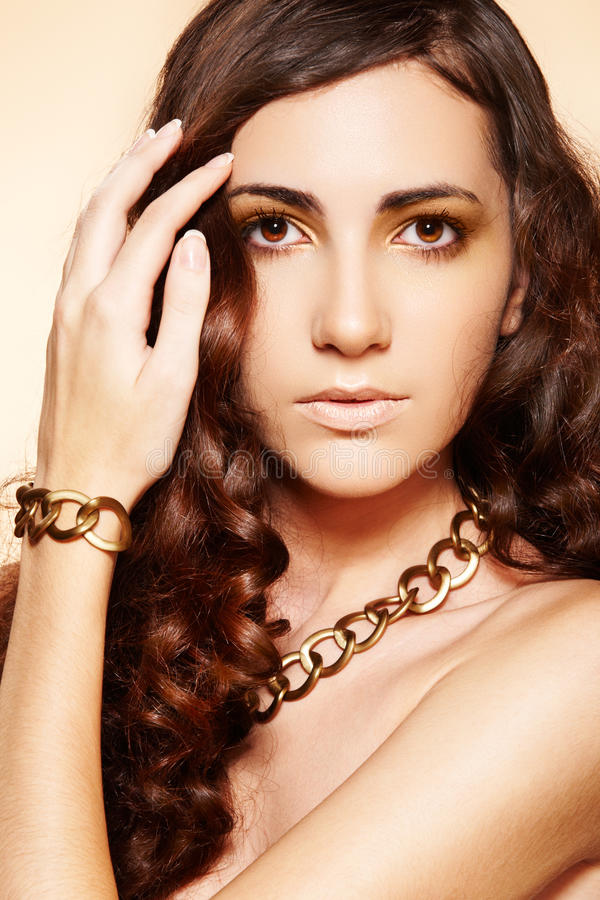 Luxury fashion woman with glamour gold accessories. Portrait of luxury fashion woman with glamour gold necklace and bracelet, brunette curly hairstyle on beige stock image