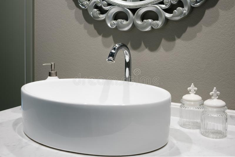 Luxury faucet mixer on a round bowl white sink in a beautiful beige gray bathroom.  stock photo