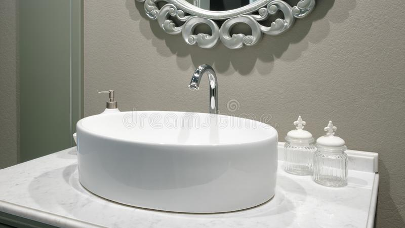 Luxury faucet mixer on a round bowl white sink in a beautiful beige gray bathroom.  stock photography