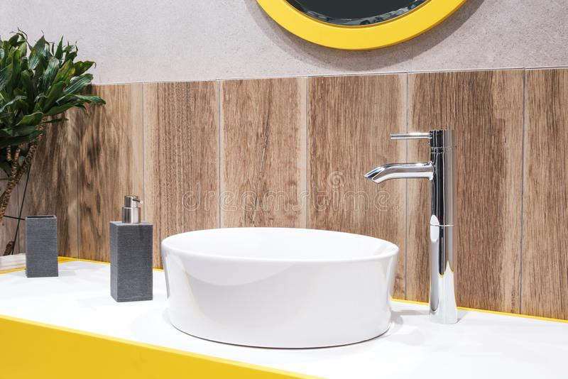 Luxury faucet mixer on a round bowl white sink in a beautiful beige wooden and yellow colour bathroom.  royalty free stock image