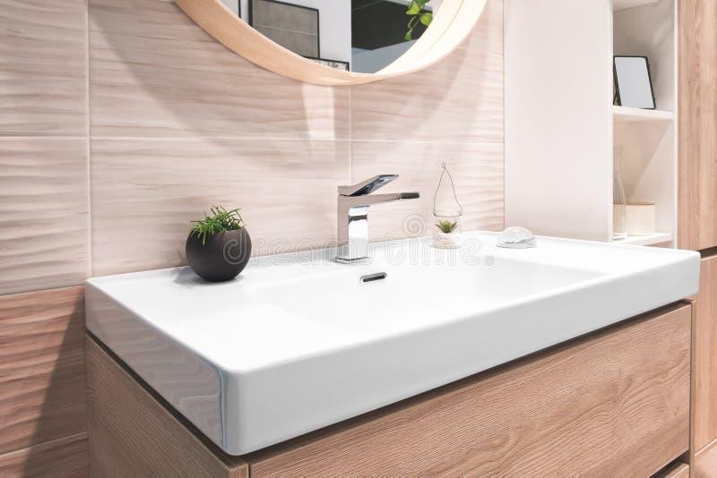Luxury faucet mixer on white rectangular sink in interior of beautiful beige gray bathroom.  stock image