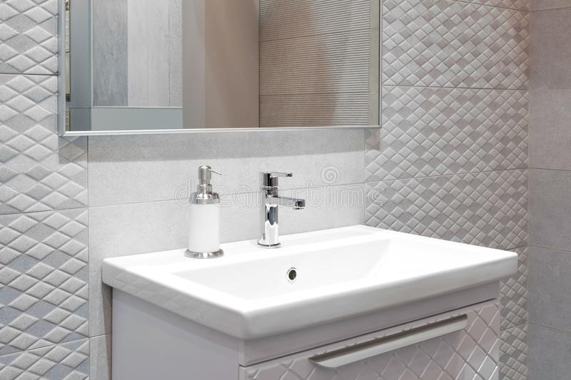 Luxury faucet mixer on a white sink in a beautiful beige gray bathroom.  royalty free stock images