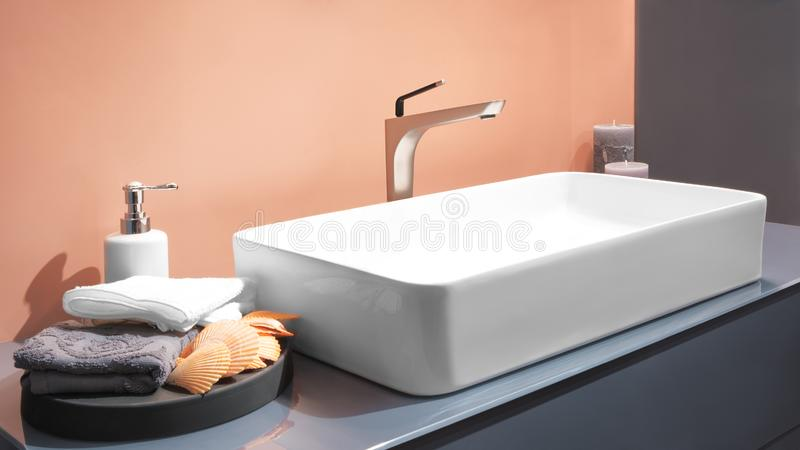Luxury faucet mixer on a white sink in a beautiful beige gray bathroom.  royalty free stock image