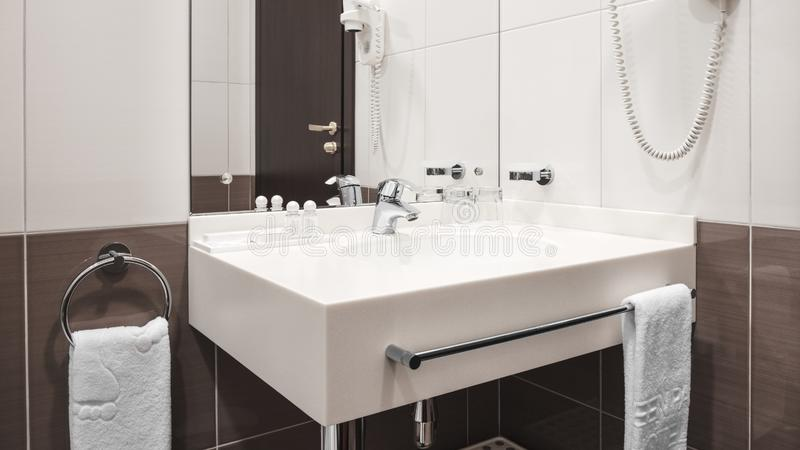 Luxury faucet mixer on a white sink in a beautiful beige gray bathroom.  stock photography