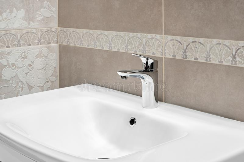 Luxury faucet mixer on a white sink in a beautiful beige gray bathroom.  royalty free stock photography