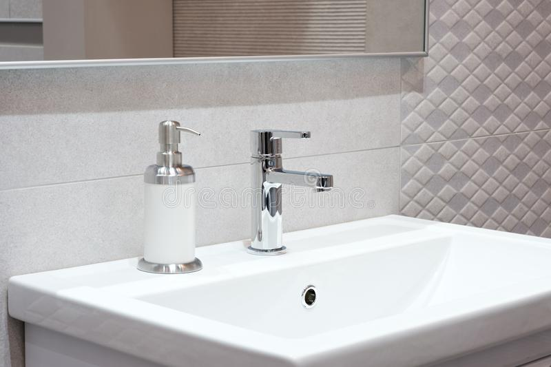 Luxury faucet mixer on a white sink in a beautiful beige gray bathroom.  royalty free stock photo