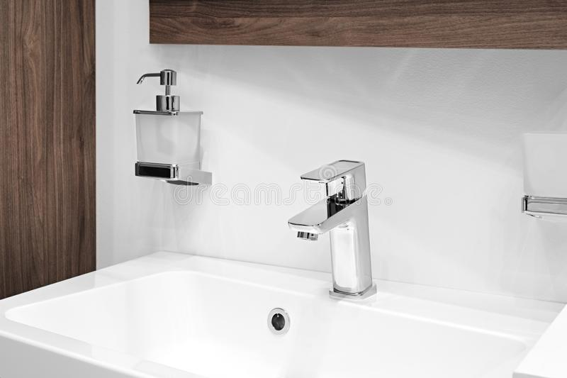 Luxury faucet mixer on a white sink in a beautiful beige gray bathroom.  stock images
