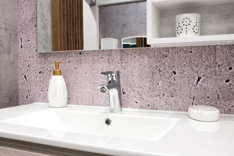 Luxury faucet mixer on a white sink in a beautiful violet gray bathroom.  royalty free stock photography