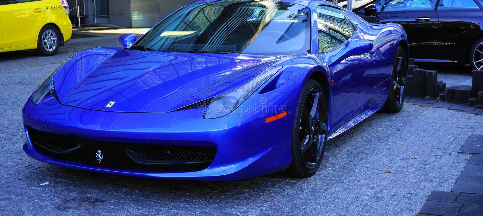 Luxury Ferrari blue car parked at the entrance of the Fairmont Pacific Rim hotel in Downtown Vancouver. royalty free stock image