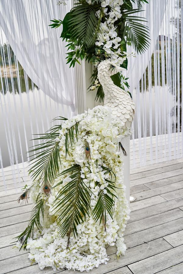 Luxury floral decor for wedding ceremony with palm leaves, orchid flowers and peacocks near water outdoors, copy space. Arch decorations, beautiful, white stock image