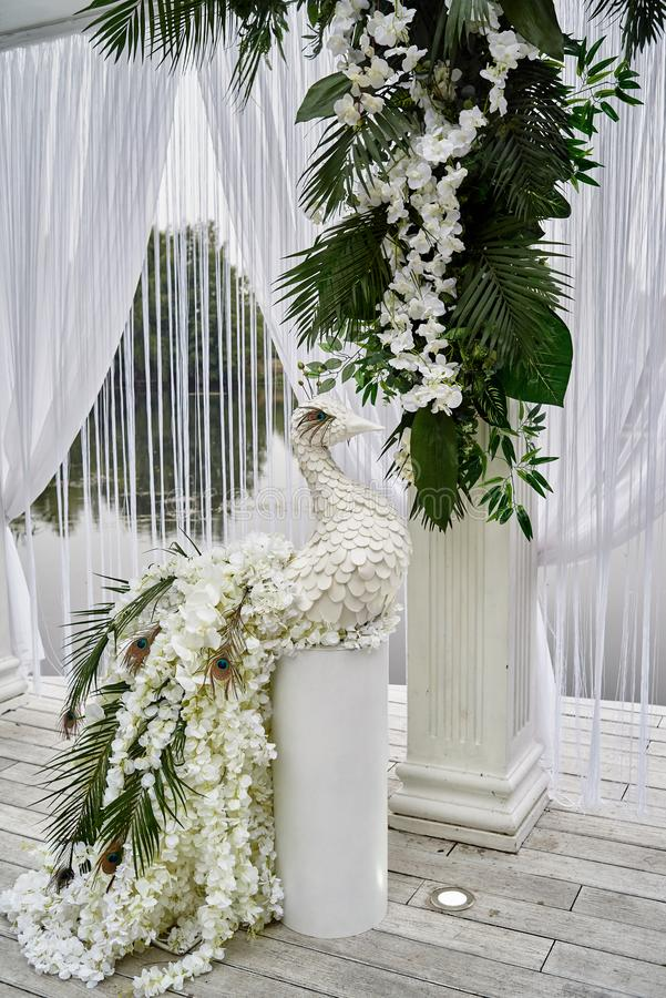 Luxury floral decor for wedding ceremony with palm leaves, orchid flowers and peacocks near water outdoors, copy space. Arch decorations, beautiful, white royalty free stock photos