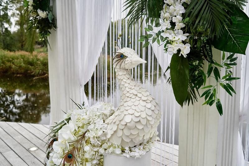 Luxury floral decor for wedding ceremony with palm leaves, orchid flowers and peacocks near water outdoors, copy space. Arch decorations, beautiful, white royalty free stock images