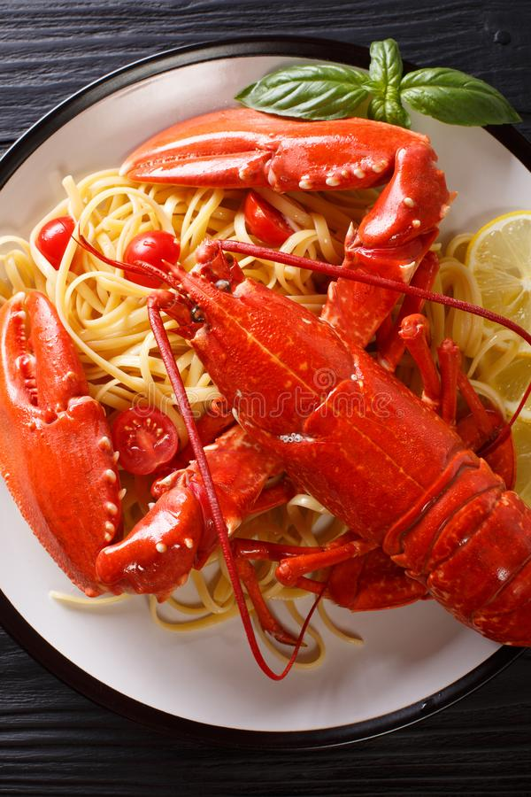 Luxury food recipe: spaghetti and boiled lobster, tomatoes, lemon and fresh herbs close-up on a black background. Vertical top vi stock image