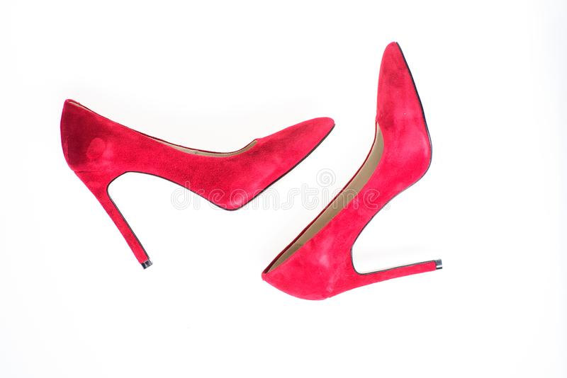 Luxury footwear concept. Footwear with thin high heels, stiletto shoes, top view. Shoes made out of red suede on white stock images