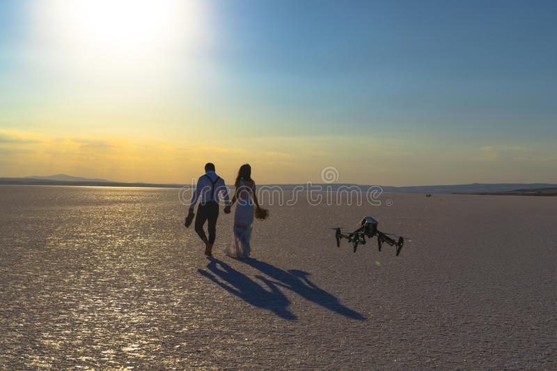 Luxury and futuristic wedding photography and videography. Hovering drone taking pictures of wedding couple at Salt Lake, royalty free stock photos