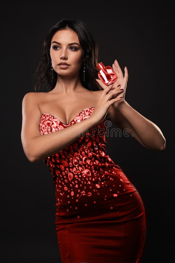 Luxury girl with a bottle of perfume in the hands on a dark background royalty free stock images